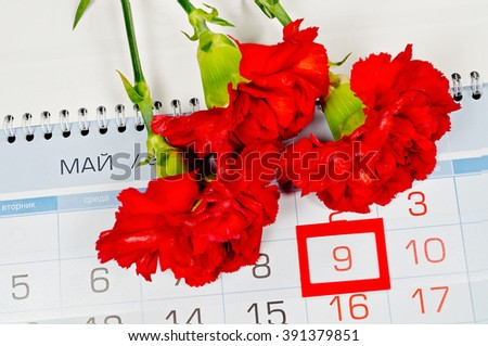 9 May concept. Bouquet of bright red carnations above the calendar with framed 9th May date - the day of USSR victory in Great Patriotic War in Russia. 9 May greeting card.  - stock photo