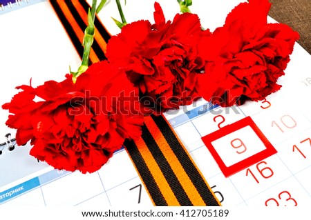 9 May concept. Postcard for Victory Day in Great Patriotic War in Russia- St George ribbon and red carnations over the calendar with framed 9th May date  - stock photo