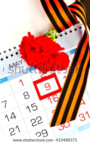 9 May concept. Red carnation wrapped with George ribbon lying on the calendar with framed 9 May date. Victory Day card - stock photo