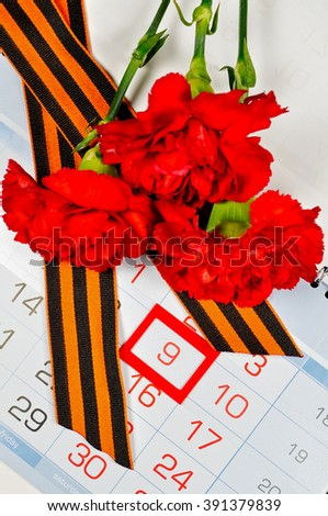 9 May concept. St George ribbon and red carnations above the calendar with 9th May date - the day of victory in Great Patriotic War in Russia.9 May greeting card.  - stock photo