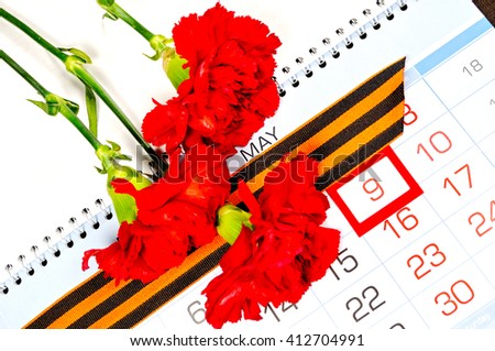9 May concept. St George ribbon and red carnations above the calendar with 9th May date - the day of victory in Great Patriotic War in Russia. 9 May festive still life.  - stock photo