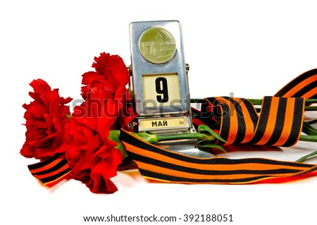 9 May concept. Vintage metal desk calendar with 9th May date and George ribbon with red carnations bouquet -  Victory Day concept isolated on white background. Selective focus at the calendar.  - stock photo