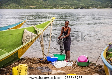 2017 May 14:Fishing village,Takawiri Island,Lake Victoria,Kenya.Water's edge.Boats beached after fishing.African woman standing, hand washing clothes in bucket. Clean cooking dishes stacked in bucket.