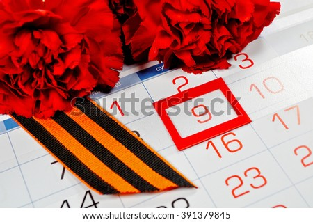 9 May greeting card. St George ribbon and red carnations above the calendar with 9th May date - the day of victory in Great Patriotic War in Russia. 9 May concept.  - stock photo