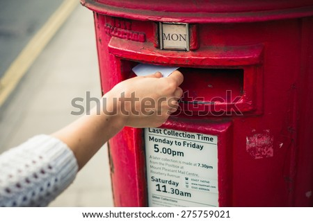 2 May 2015, London, United Kingdom - A female hand is posting a letter in a mail box belonging to Royal Mail - stock photo