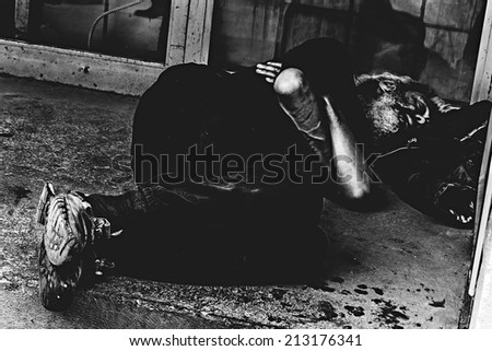 14-MAY-2014 Montreal,Canada-Homeless person sleeping at the St.Catherine street during the day in black and white - stock photo