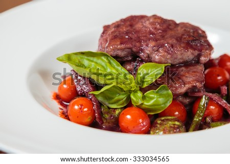 Meat sauce with vegetables in a beautiful exposition on a white plate. Tender meat and fresh vegetables. Appetizing and tasty dish. Photo for culinary magazines, posters, backdrops and websites.  - stock photo