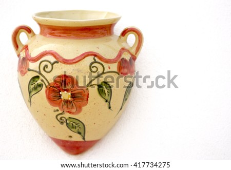 mediterranean souvenirs, single painted decorative pots. Shot in shallow depth of field, colours of orange cream and green on a white wall, room for text ideal for a poster, menu or a holiday event - stock photo