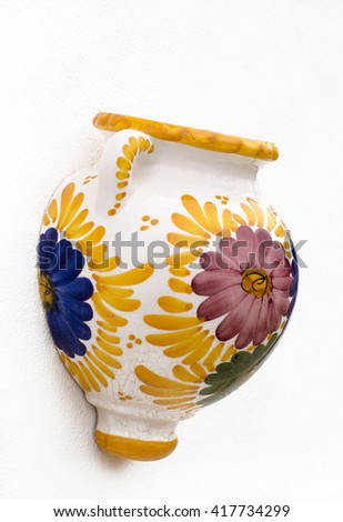 mediterranean souvenirs, single painted decorative wall pot. Shot in shallow depth of field in the colors of yellow,blue green and purple on a white wall background, with room for text   - stock photo