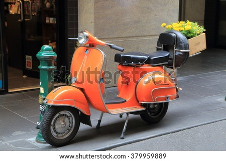 MELBOURNE AUSTRALIA - FEBRUARY 13, 2016: Orange Vespa scooter parked on street in Melbourne.  - stock photo
