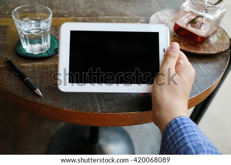 men hand presses the blank screen tablet computer. Concept man working from home or cafe using tablet computer.  internet of things,  wireless communication and internet with smart phone. - stock photo