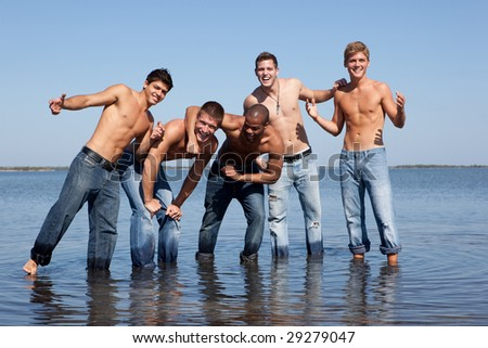5 men in jeans at the beach, standing in the water - stock photo