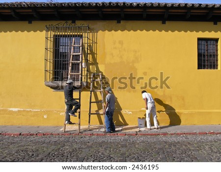 men paintig house in antigua - stock photo