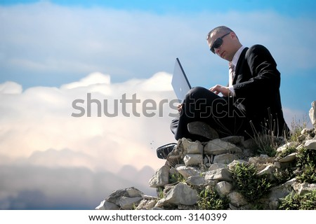 Men with his laptop working on a stone wall - stock photo