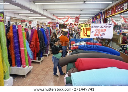 Merida, Yucatan Mexico, January 22, 2015: Shoppers sort through colorful material in a fabric store in Merida Mexico.                               - stock photo