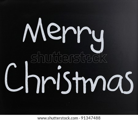 """Merry Christmas"" handwritten with white chalk on a blackboard - stock photo"