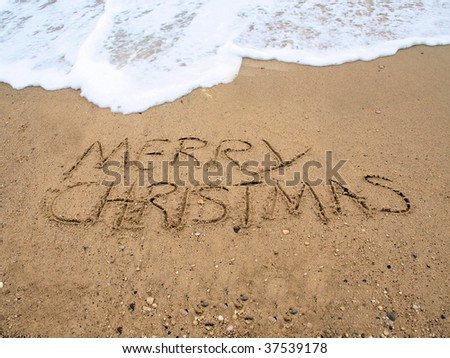 Merry Christmas written on the beach in the sand - stock photo