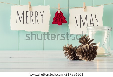 """Merry xmas"" and a felt tree hanging on a rope with clothespins. A robin egg blue wainscot as background and some pinecones and a candle on a white wooden table. Vintage Style. - stock photo"