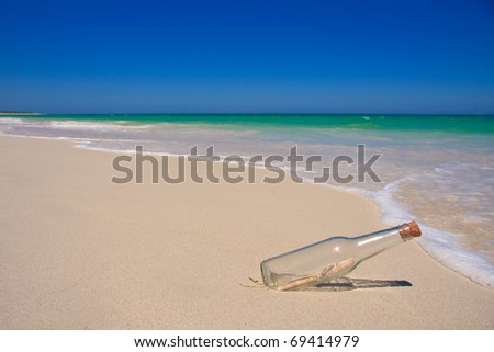 'Message in a Bottle' on a beautiful beach - stock photo
