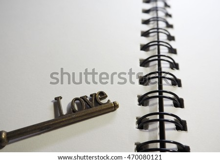 Metal brass key chain with the word LOVE on a blank notebook in cool tone color filter
