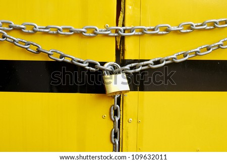metal chain and lock on yellow background - Key lock locked with a chain - - stock photo