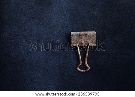 metal grunge paper clip on black leather background - stock photo