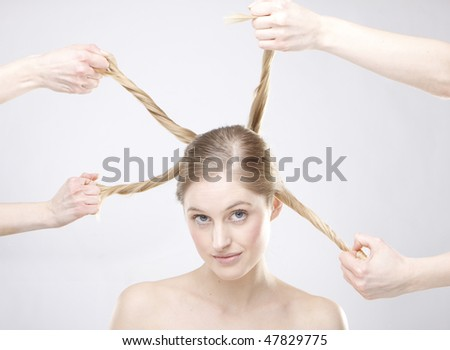 metaphorical image of hands holding different styles of rolls of a blond woman's hair. - stock photo