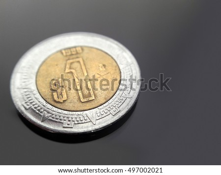 1 Mexican Peso on dark glossy surface.