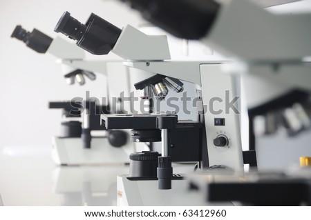 3 microscopes in laboratory for micro organisms. - stock photo