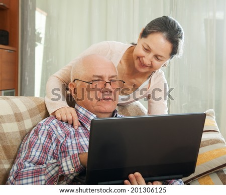 middle-aged man and woman sitting on  couch with  laptop - stock photo