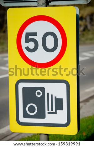 50 miles speed limit and black and white speed camera warning sign - stock photo