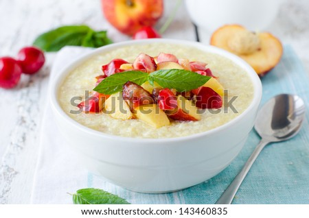 Milk porridge with peaches and cherries. Selective focus - stock photo