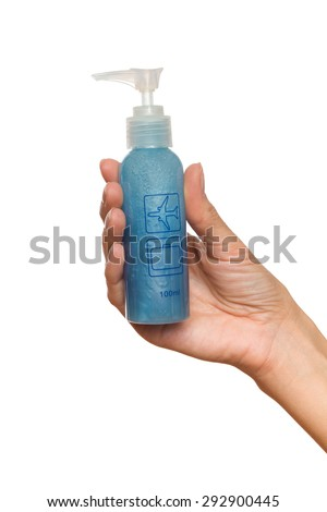 100ml Bottle Carry-on Baggage Restrictions. Close up of woman's hand holding a 100ml plastic bottle with blue liquid. Studio shot isolated on white. - stock photo