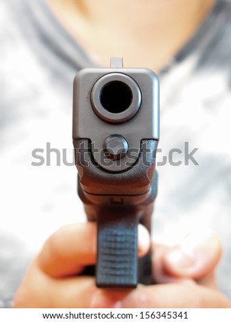 9 mm automatic hand gun holding by woman hands in extreme close up macro. Self defense concept. - stock photo