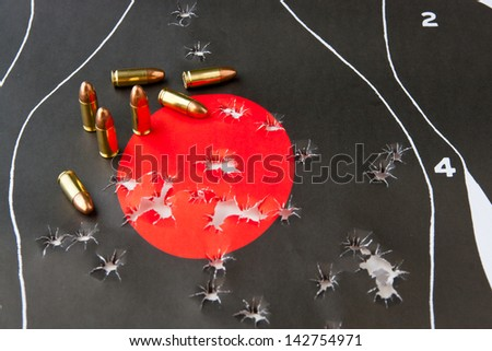 9 mm bullets and bullet holes in the target - stock photo