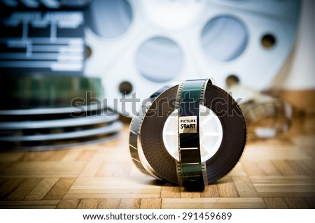 35 mm cinema movie filmstrip with picture start frame and other movie objects background - stock photo