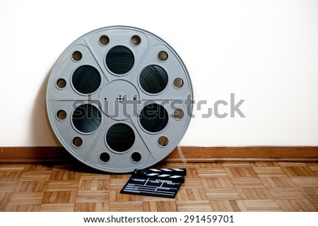 35 mm cinema movie roll with clapper on wooden floor and white wall background - stock photo