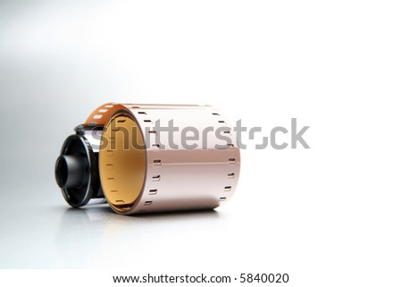 35mm film roll, closeup on brushed metal - stock photo