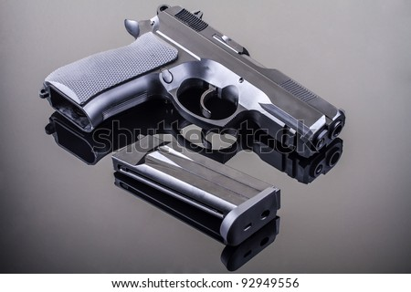 9 mm hand gun on glass table with reflection - stock photo