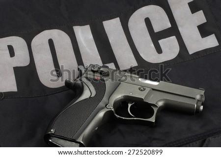 9mm handgun with ammo on police uniform - stock photo