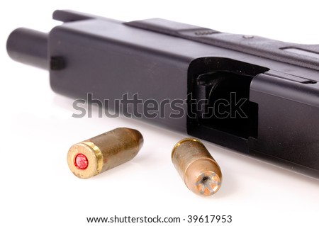 9mm hollow point bullet and a pistol with the slide back on a white background - stock photo