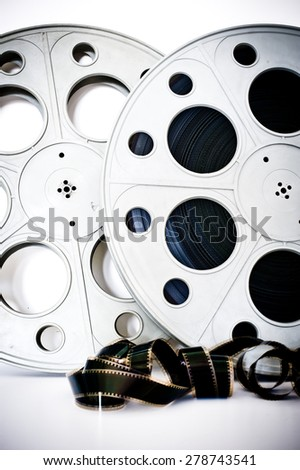 35 mm movie cinema reels with film unrolled vertical frame on white background - stock photo