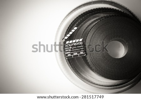 35 mm movie film reel  with little clapper, black and white with copy space - stock photo