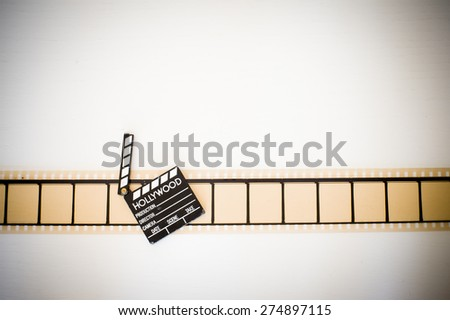 35mm movie filmstrip blank frames reel with clapper board vintage color effect horizontal - stock photo