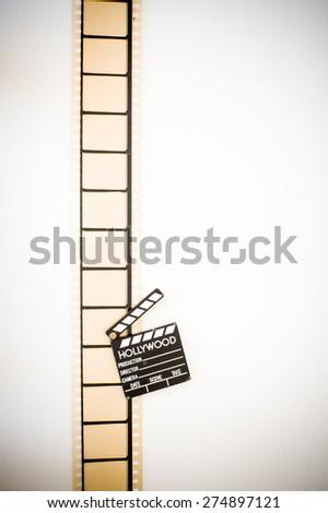 35mm movie filmstrip blank frames reel with clapper board vintage color effect vertical - stock photo