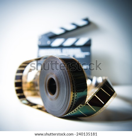 35mm movie reel with out of focus clapper in background, color effect and vintage look - stock photo