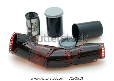 35 mm negative film and canisters isolated in white background - stock photo