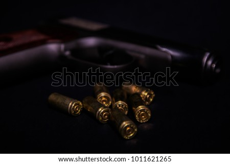 9 mm pistol gun and bullets strewn on black background. Bullets isolated