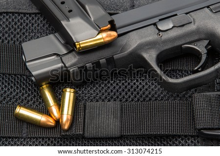 9 mm tactical handgun and modular lightweight load carrying bullet proof vest with full spare magazine clip and loose ammunition - stock photo