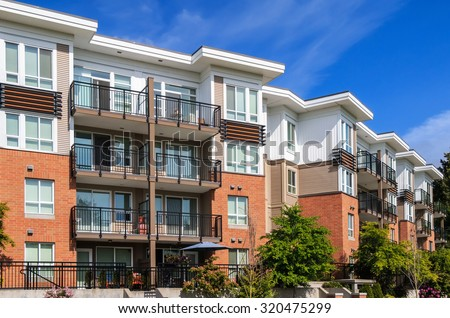 Modern apartment building in sunny day against blue sky. - stock photo